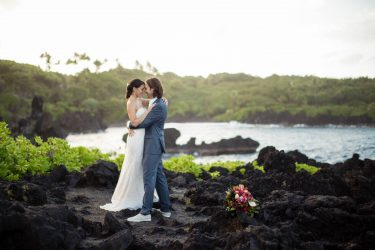 Newly married couple with Waianapanapa's black sand beach in the background